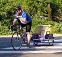 Cyklist med Cykelkärra ute i trafiken