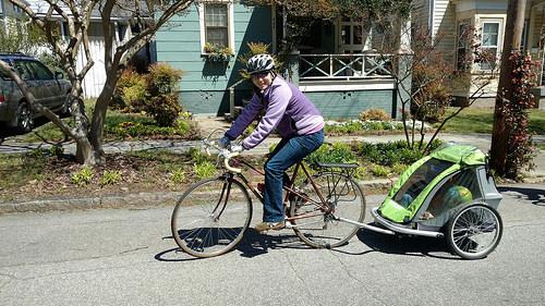 Dam med cykel och barn i cykelkärran